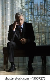 Businessman in suit with serious expression sitting talking on a mobile phone. Vertical shot.