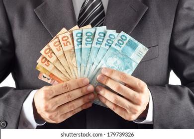 A businessman in a suit showing brazilian money