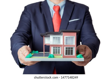 businessman in suit showing house model  in hand isolated on white background