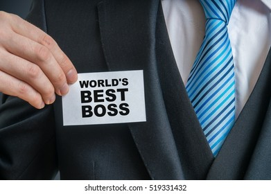 Businessman in suit is showing label that He is worlds best boss ever.