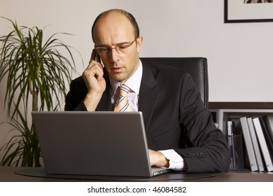 Businessman in suit sitting at desk in office engaged in work on laptop and talking on cell phone