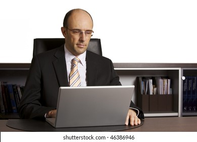 Businessman in suit sitting at desk in office engaged in work on laptop, white background