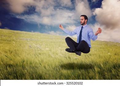 Businessman in suit sitting in lotus pose against nature scene
