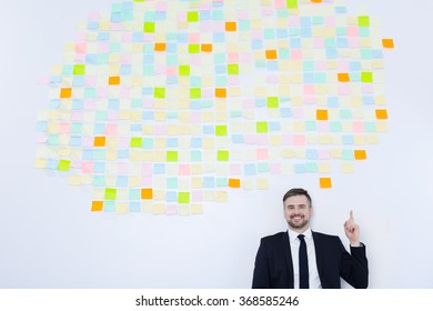 Businessman in suit smiling, standing on sticky notes background