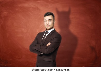 Businessman in suit standing with his arms folded, he is casting shadow of the devil on the rusty orange wall behind him. Unfair competition. Aggressive marketing strategies. Hidden motives.
