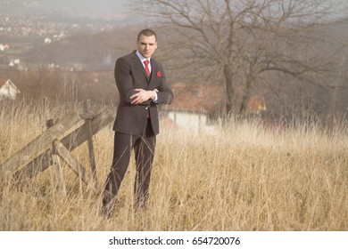 Businessman in a suit standing on a spacious gorgeous field. Men in a field with sunlight. Businessman in nature.