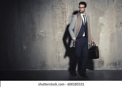 Businessman in suit standing in shadowy studio