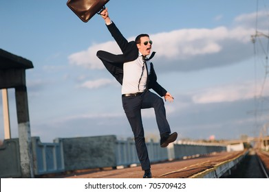 a businessman in a suit with a suitcase rejoices in successes in his career. Good news.