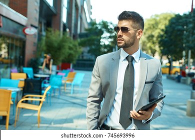 Businessman in suit and sunglasses walking on street holding digital tablet.