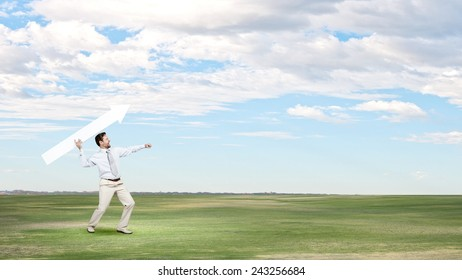 Businessman in suit throwing white blank arrow in hands
