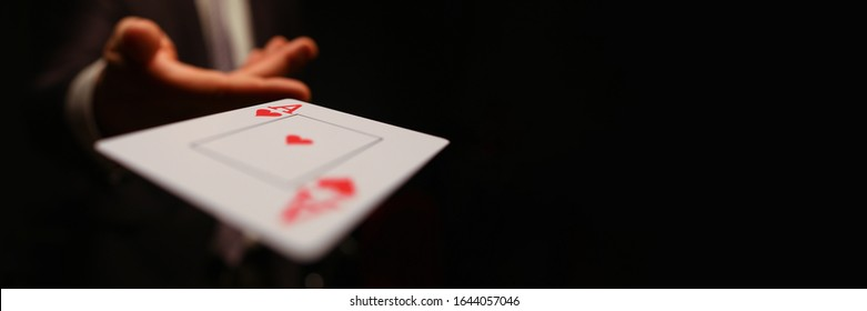Businessman in suit throws his hand playing card ace of worms to opponent on a black background. Winning in business payout concept