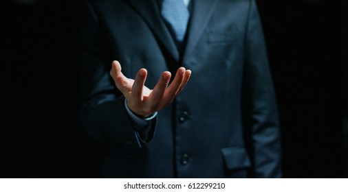 a businessman in a suit and tie with outstretched hand for implementation of graphic futuristic. Concept: business, graphic, holography, alpha channel.