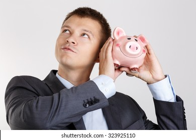 Businessman in suit and tie shaking funny piggybank and listening sound of inside detecting amount. Budgeting expenses concept. Making savings and effective investment concept. Future needs deposit