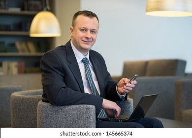 A businessman in suit and tie sitting on a chair with laptop and phone