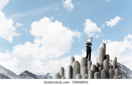 Businessman in suit with TV instead of head keeping arms crossed while standing on the top of stone columns with beautiful landscape on background.