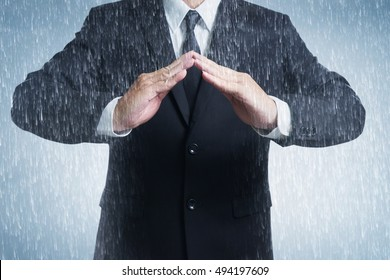 Businessman in suit with two hands in position to protect in rainy weather day. It indicates many aspects such as car insurance coverage, support, assurance, reliability.