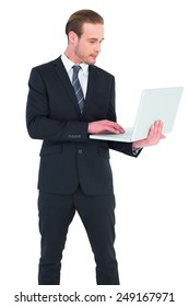Businessman in suit typing on laptop on white background