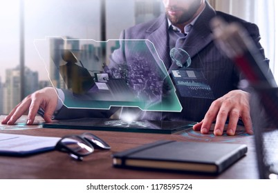 A businessman in a suit uses holography and augmented reality to see the conference of financial economics in his office. Concept: immersive technology, business, economy, futuristic conference