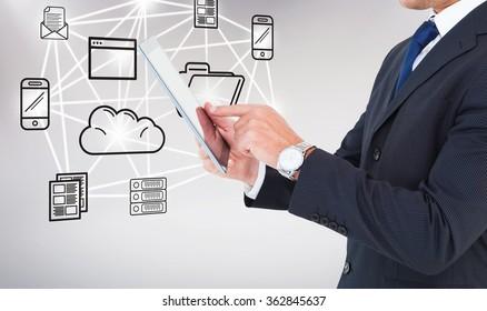 Businessman in suit using digital tablet against grey background