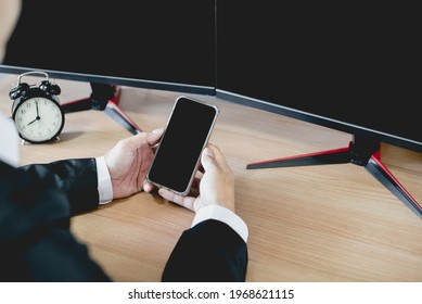 A businessman in a suit using a smartphone and a computer to work at home. Work from home cocept.tif
