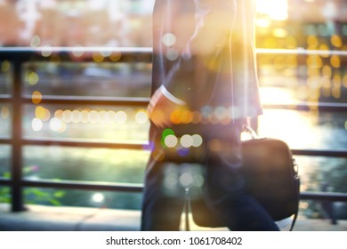 Businessman in suit walking in the City against of sunset. Business and modern life concept.