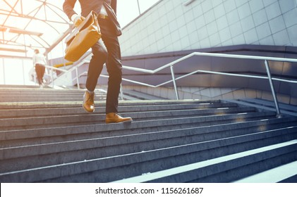 Businessman in suit walking down on concrete steps. Stylish business worker wearing formal clothes making his way down steps.  Business concept for office workers and corporate stuff.