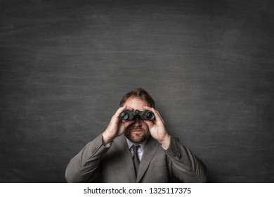 Businessman in a suit watching with binoculars