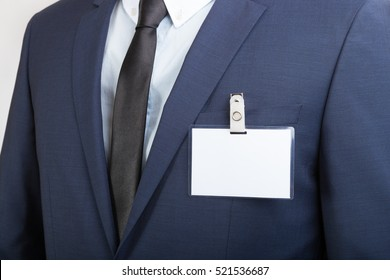 Businessman in suit wearing a blank ID tag or name card during an exhibition or a conference