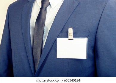 Businessman in suit wearing a blank ID tag or name card during an exhibition or a conference. Filtered image: cross processed vintage effect.