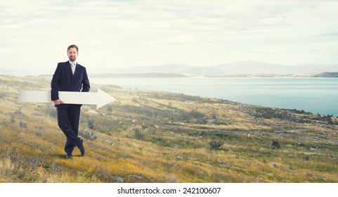 Businessman in suit with white blank arrow in hands