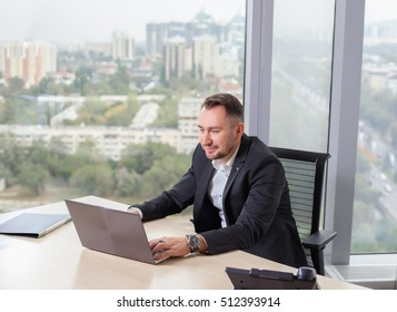 Businessman in suit working on laptop, at a table in the office