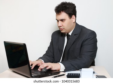 Businessman in suit works with laptop at table with paper, pen, calculator