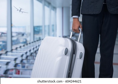 Businessman and suitcase in the airport departure lounge, airplane in the blurred background, summer vacation concept, traveler suitcases in airport terminal waiting area. .