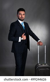 Businessman with a suitcase on grey background