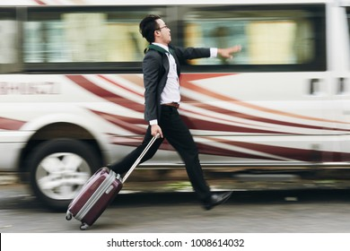 Businessman with suitcase running to catch the bus