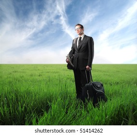 Businessman with suitcase standing on a green meadow
