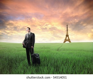 Businessman with suitcase standing on a green meadow with Eiffel Tower on the background