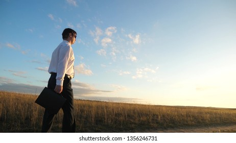 businessman in sunglasses goes down country road with briefcase in his hand. agricultural business concept. The entrepreneur works in a rural area. farmer inspects the land at sunset. Slow motion