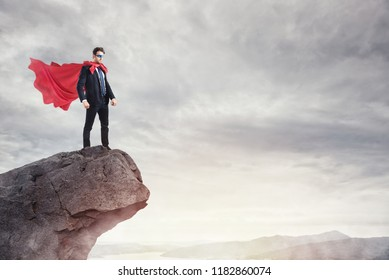 Businessman as a super hero on the peak of a mountain