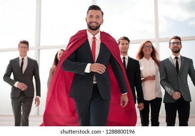 businessman is a superhero, stepping ahead of his business team