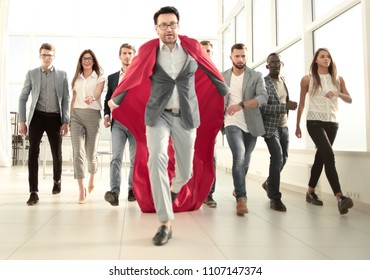 businessman in a superhero's cloak is ahead of the business team