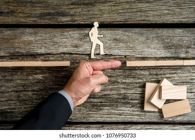Businessman supporting paper cut out of a man walking forwards to success over rustic wood background.