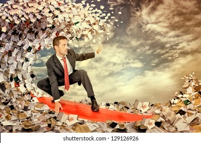 Businessman surfing in a sea made of files and papers