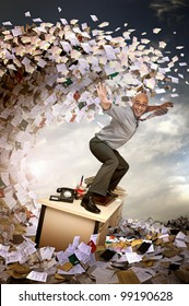 Businessman surfing in a sea of papers and files