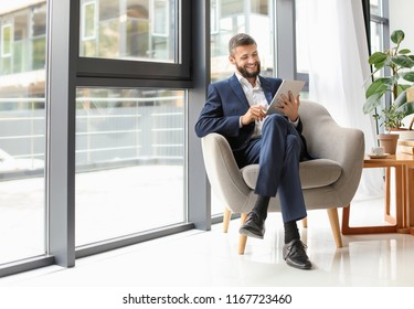 Businessman with tablet computer sitting in armchair