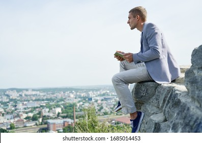 businessman with a tablet in his hands sits on a rock against the background of the city and looks into the distance