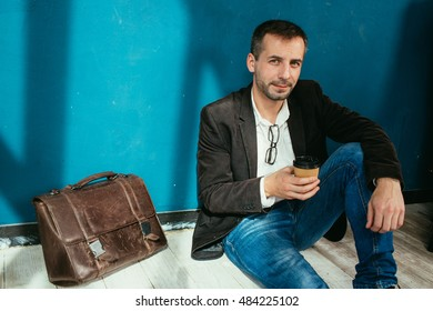 Businessman with tablet near wall