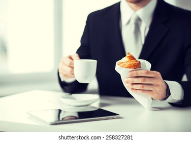 businessman with tablet pc, cup of coffee and croissant