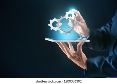 Businessman with tablet PC and digital gearwheels on dark background. Concept of Internet and technical support service