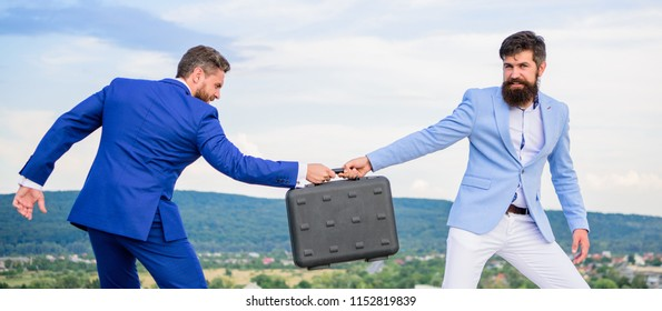 Businessman takes away briefcase from business partner. Fraud and extortion concept. Man cheating while handover meeting. Men in suits handover briefcase. Business deal landscape background.